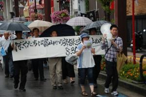 出発集会で書いた戦争法案反対のメッセージを広げてパレードする参加者