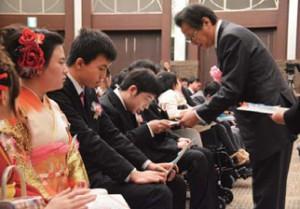 新成人一人ひとりに色紙を手渡す河合隆県善意銀行理事長