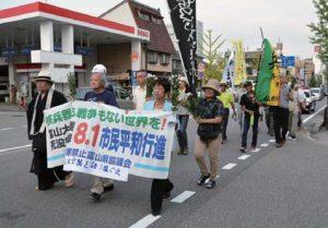 菊を手に富山大空襲の犠牲者を追悼して行進する参加者=1日、富山市