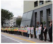歩道に一列に並んでアピールするスタンディング参加者=21日、富山市役所前