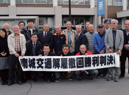 勝利判決後、富山地裁前で記念撮影する原告(前列3人)と弁護士、支援者=11月30日、富山市