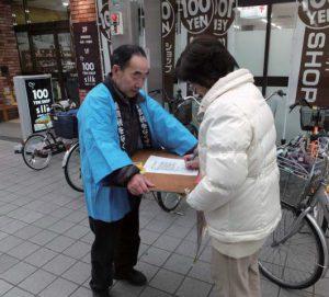 呼びかけに応えて署名する女性=3月24日、富山市