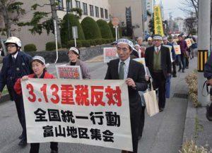 消費税10%への増税反対などを訴えて富山税務署近くまでデモ行進する参加者=13日、富山市