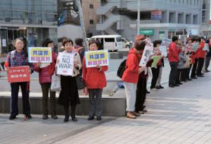 スタンディングで戦争法廃止、共謀罪反対などをアピールする参加者=18日、富山市